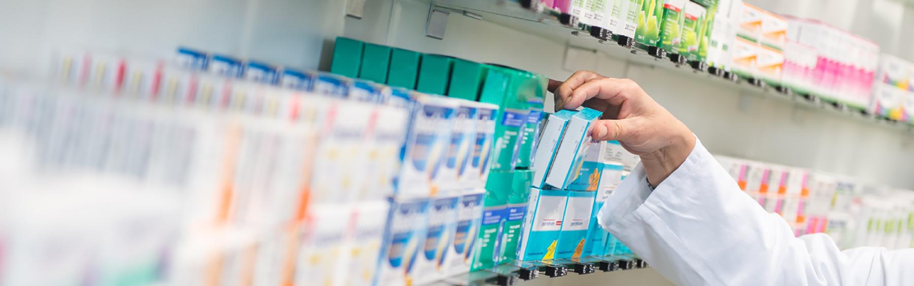 Pharmacist taking medication off of shelf